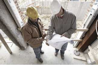 Two contractors reading blueprints