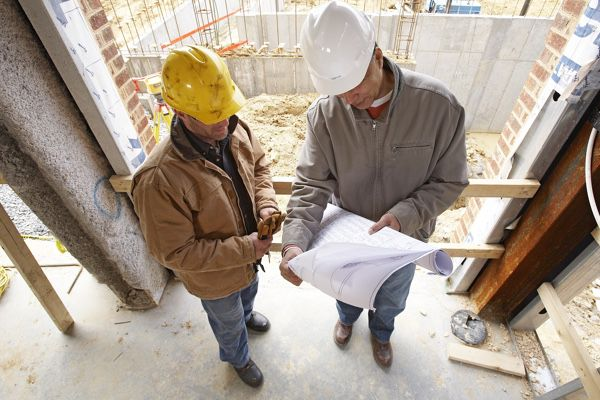 Two contractors viewing blueprints