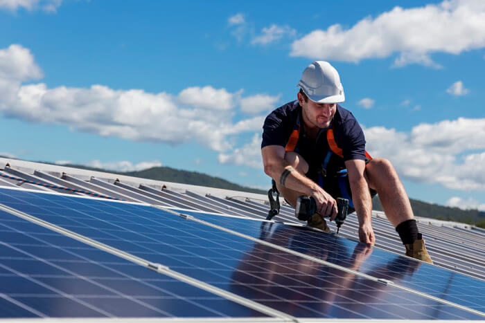 A man on roof installing solar panels